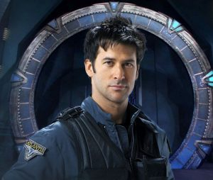 "Celebrity Fan Fest guest Joe Flanigan in blue jacket standing in front of ""Stargate: Atlantis"" portal"
